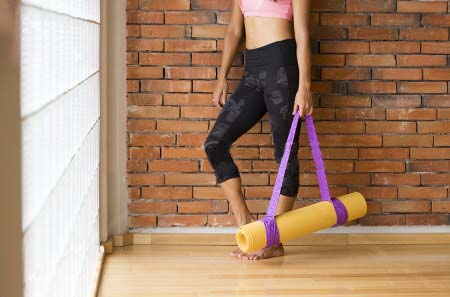 stock-photo-unrecognizable-woman-in-a-yoga-studio-indoors-against-a-brick-wall-with-a-mat-311459837
